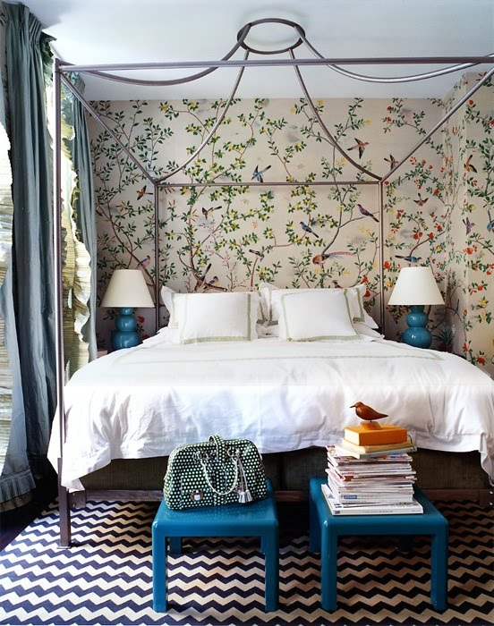Romantic bedroom with iron bedframe, black and white chevron printed rug, blue stools and floor to ceiling 19th Century sparrow wallpaper