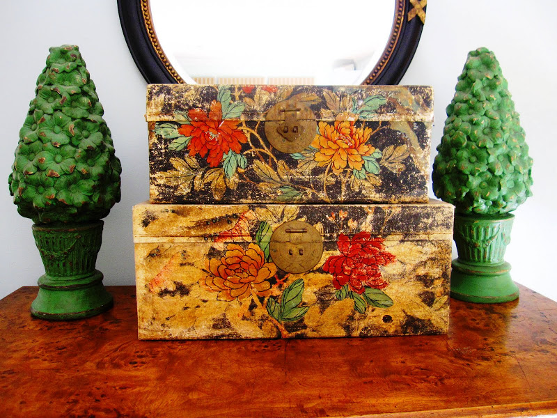 Two green wood topiaries and a two vintage floral storage boxes on an antique dresser