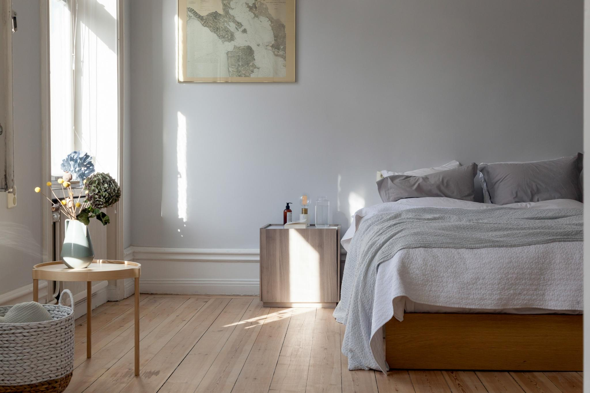 I love the soft tones in this cozy bedroom the very light grey on the bedroom wall matches perfectly with the different wood tones of the bed