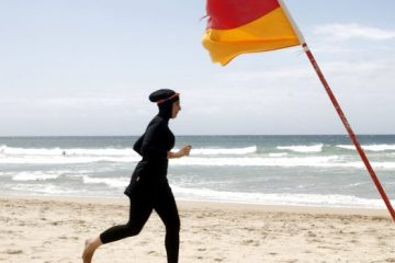 """Twenty-year-old trainee volunteer surf life saver Mecca Laalaa runs along North Cronulla Beach in Sydney during her Bronze medallion competency test January 13, 2007. Specifically designed for Muslim women, Laalaa's body-covering swimming costume has been named the """"burkini"""" by its Sydney based designer Aheda Zanetti."""