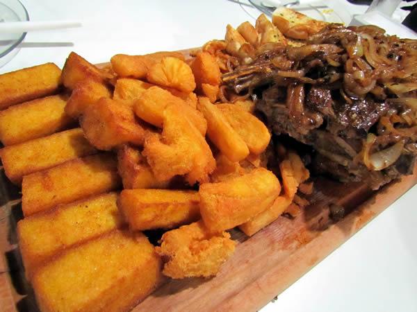Chuleta: bifes de chuleta aceboladas, polenta frita, aipim frito e pão na chapa