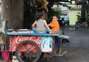 Children sitting on a food card in Bangkok, Thailand.