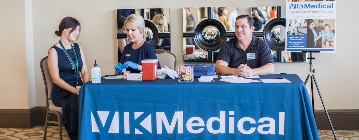 Andrea Connell (second from left), practice manager at Vik Medical Urgent Care and Family Practice, gives a flu shot at a local chamber meeting.