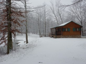 log cabin winter white out in woods with stream