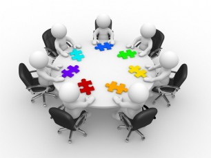 figures at a round table-colorful puzzle pieces
