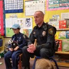 Officer Colin and retired chief John Barber speak to a kindergarten class in Northeast Elementary School.