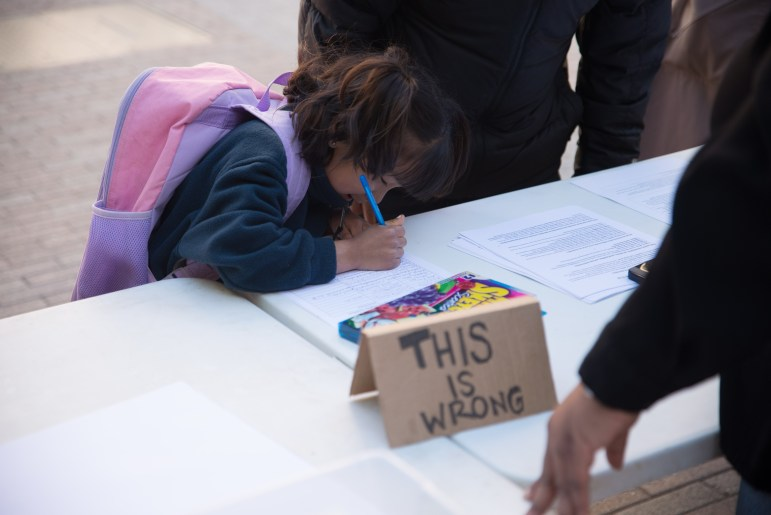 Mila Oshe signs up for an ICE-out information sheet during a rally on the Ithaca Commons.