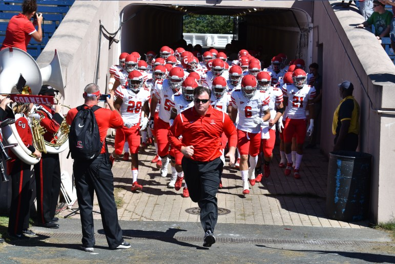 Head coach David Archer '05 leads his team out to their first Ivy action of the season against Yale. The Bulldogs won, 49-24.