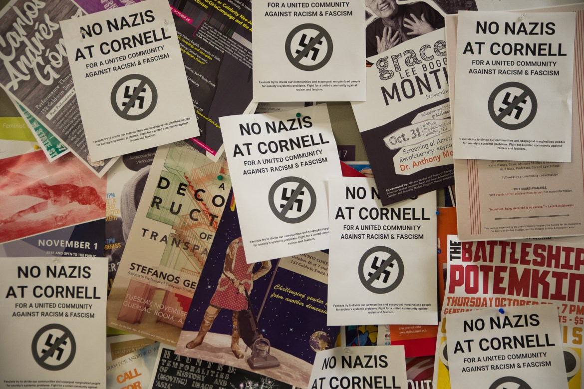 "Posters reading ""No Nazis at Cornell"" punctuate dozens of other advertising posters at the entrance to Goldwin Smith Hall on Oct. 24, 2017."