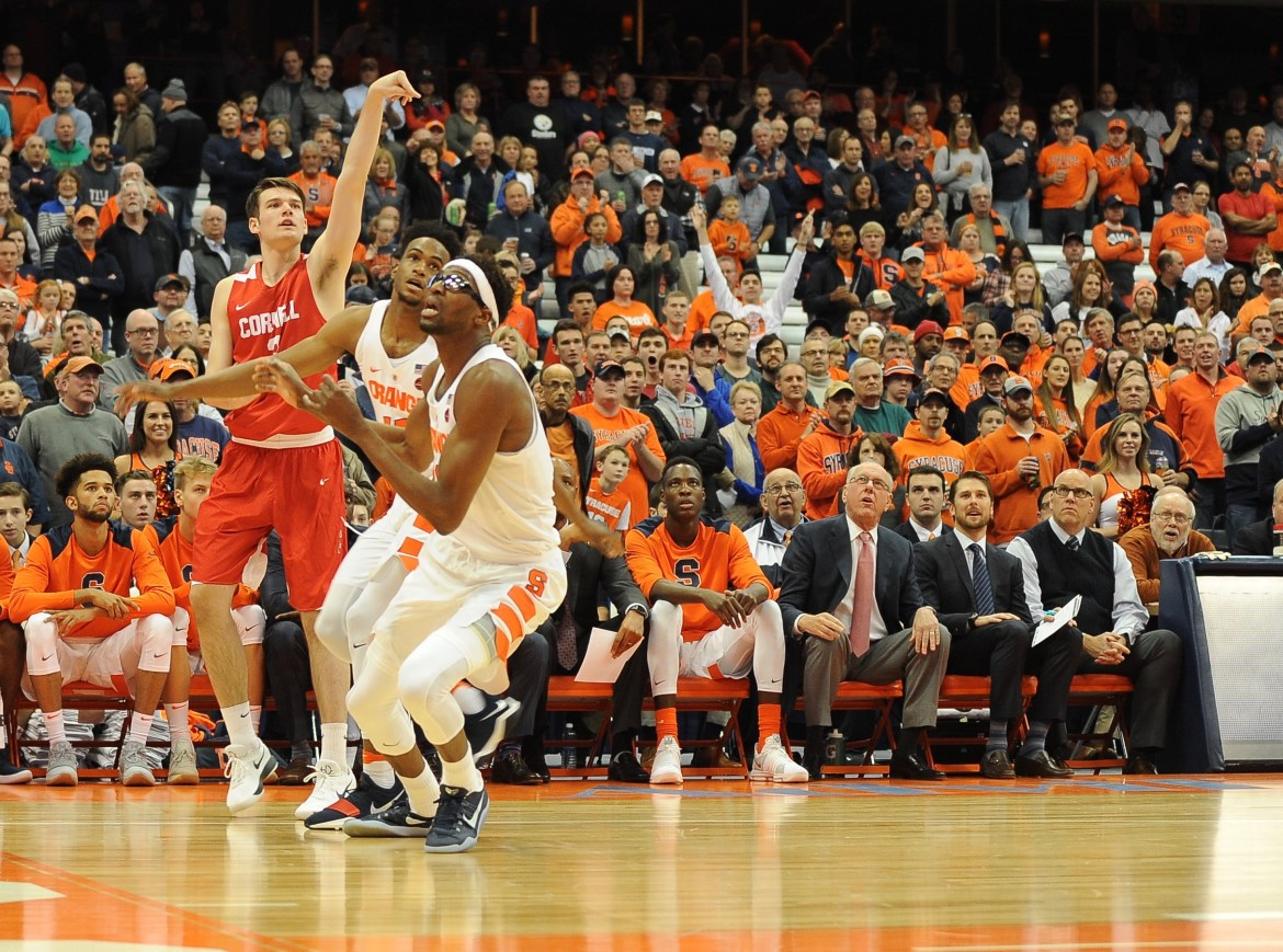 Cornell freshman Jimmy Boeheim (#3) sinks Cornell's first points of the season and the first points of the game with his father, Syracuse coach Jim Boeheim, looking on.