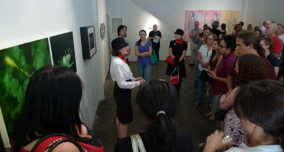 """Julia Bradshaw, Curator and flight-attendant, explains the concept behind the exhibition """"Air Travel"""" to opening reception visitors."""