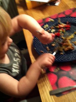 Hur man håller bestick. Ett under att hon fick upp något på gaffeln alls, men efter ett tag var tallriken tom.
