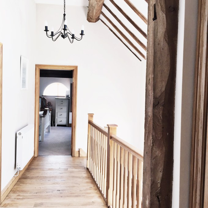 Landing in the barn with exposed beams and an oak floor