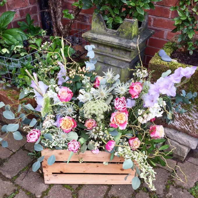 Wooden crate with roses, thistles and eucalyptus