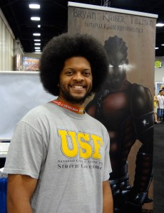 Bryan Tillman standing before a vinyl hanging at Comic-Con in San Diego promoting Dark Legacy