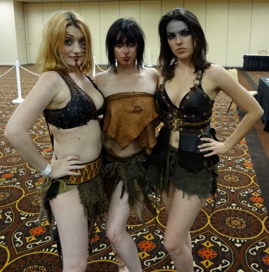 Three scantily-clad women cosplaying as barbarians in furs and leather in the Combat Con Vendors' Hall