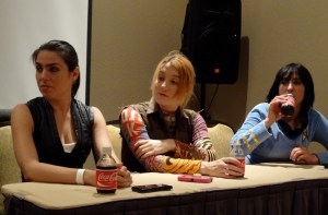 Three attractive female cosplayers sitting at a table at the Cosplay panel at Combat  Con