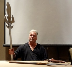 David Baker holding a metal spear with sharp edges at a 2012 Combat Con cosplay panel
