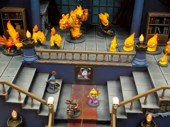Three Cartoonish Dungeon Explorer Miniatures in Cool Mini's Super Dungeon Explore castle with fire elementals at gen con 2012