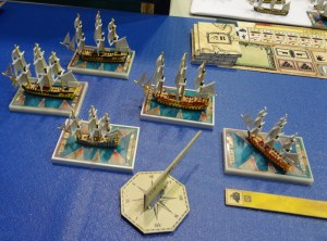 Model miniature ships battle in Sails of Glory on blue mat representing ocean