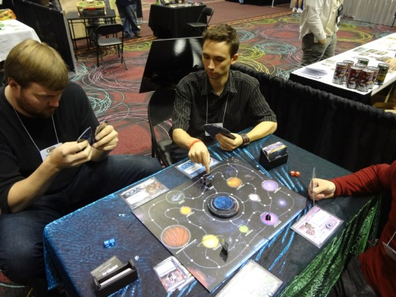 Diagonal view of board game Chaosmos with 10 planets and play pieces at GAMA Trade Show with three players
