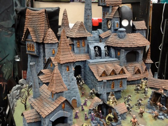 Wrath of Kings miniatures fight over a superb Goritsi city at Gen Con 2012 in front of stone buildings with red tiled roofs