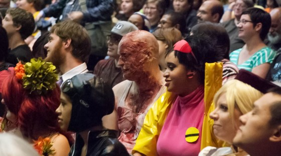 Horribly burnt Zombie cosplayer Andrew Myers next to smiling yellow trenchcoat wearing Jubilee in crowd at costume contest
