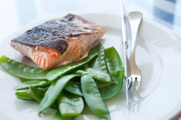 Cooked fresh salmon steak served with delicious sugersnap peas, closeup view with shallow dof