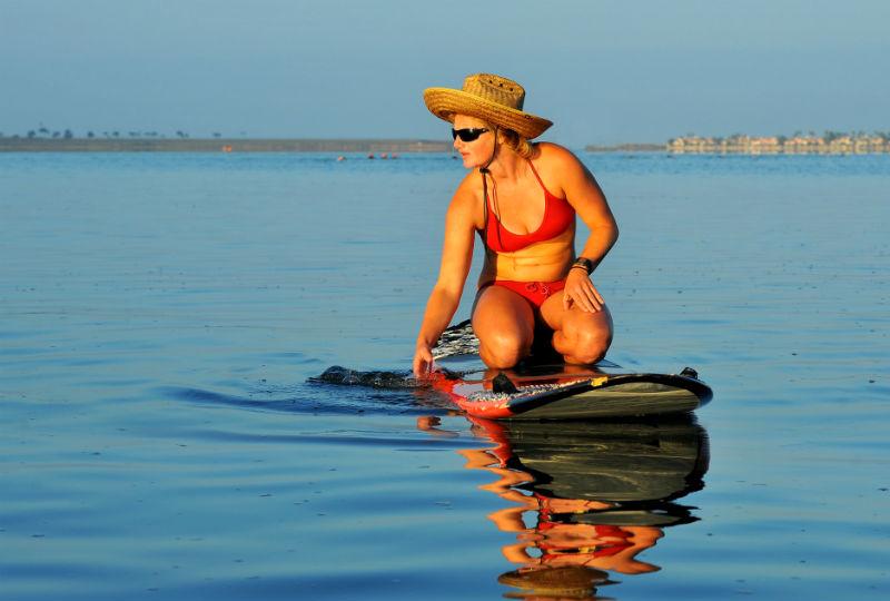 girl on bikini kneeling on padddleboard