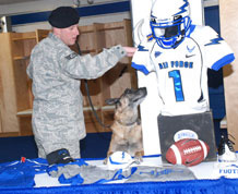 Staff Sgt. Gary Resta and his dog, Odys, search for explosives in the Falcons football locker room as part of a dog bomb-sniffing competition Feb. 17. Photo by Ann Patton