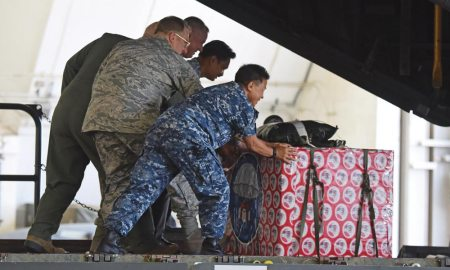 U.S. Air Force photo/Airman 1st Class Jacob Skovo Military and civilian leaders push a box onto a C-130 Hercules during the 2016 Operation Christmas Drop Push Ceremony Dec. 6, 2016, at Andersen Air Force Base, Guam. This year the Japan Air Self-Defense Force, Royal Australian Air Force and U.S. Air Force worked together to continue the tradition of air dropping tools, food, clothing and toys throughout the Pacific.