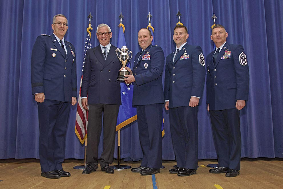 (U.S. Air Force photo by Airman 1st Class Dennis Hoffman) PETERSON AIR FORCE BASE, Colo. –Col. Doug Schiess, 21st Space Wing commander, accepts the Omaha Trophy from Gen. John Hyten, U.S. Strategic Command commander, and Mogens Bay, Strategic Command Consultation Committee, on behalf of the 21st SW during a ceremony in the auditorium on Peterson Air Force Base, Colo., April 6, 2017. This was the first time the 21st SW received the award since its inception in 2008.