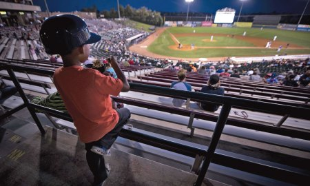 (U.S. Air Force photo by Senior Airman Dennis Hoffman) Colorado Springs, Colo. — A boy attending a Snowflake Event at Security Service Field watches a Sky Sox baseball game while eating ice cream in Colorado Springs, Colo., Aug. 21, 2017. A Snowflake event is a regional occurrence hosted for Snowball Express families. Since 2006, Snowball Express has provided hope and happy memories to the children of military fallen heroes who have died while on active duty since 9/11.