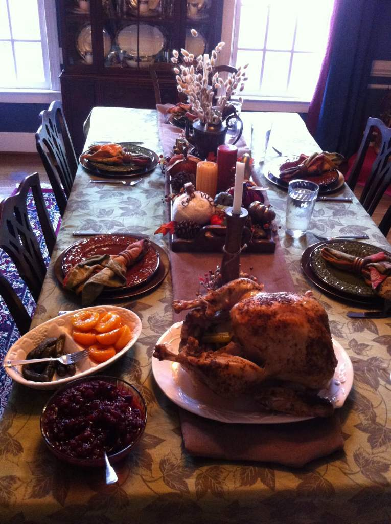 Setting the Thanksgiving dinner table: turkey and many sides