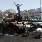 Boys stand on a tank burnt during clashes on a street in Yemen's southern port city of Aden March 29, 2015