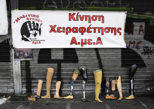 "Prosthetics are placed in front of the Labour Ministry by disabled people during the 24-hour general strike. The banner reads, ""Movement for emancipation of people with special needs""."