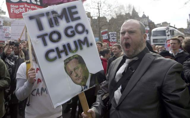 Demonstrators hold placards during a protest outside Downing Street in Whitehall, central London