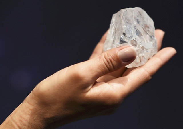 "A model shows off the 1109 carat ""Lesedi La Rona"", the largest gem quality rough diamond discovered in over 100 years during a sale preview at Sotheby's auction house in London"