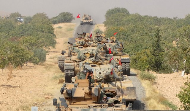Turkish army tanks make their way towards the Syrian border town of Jarablus