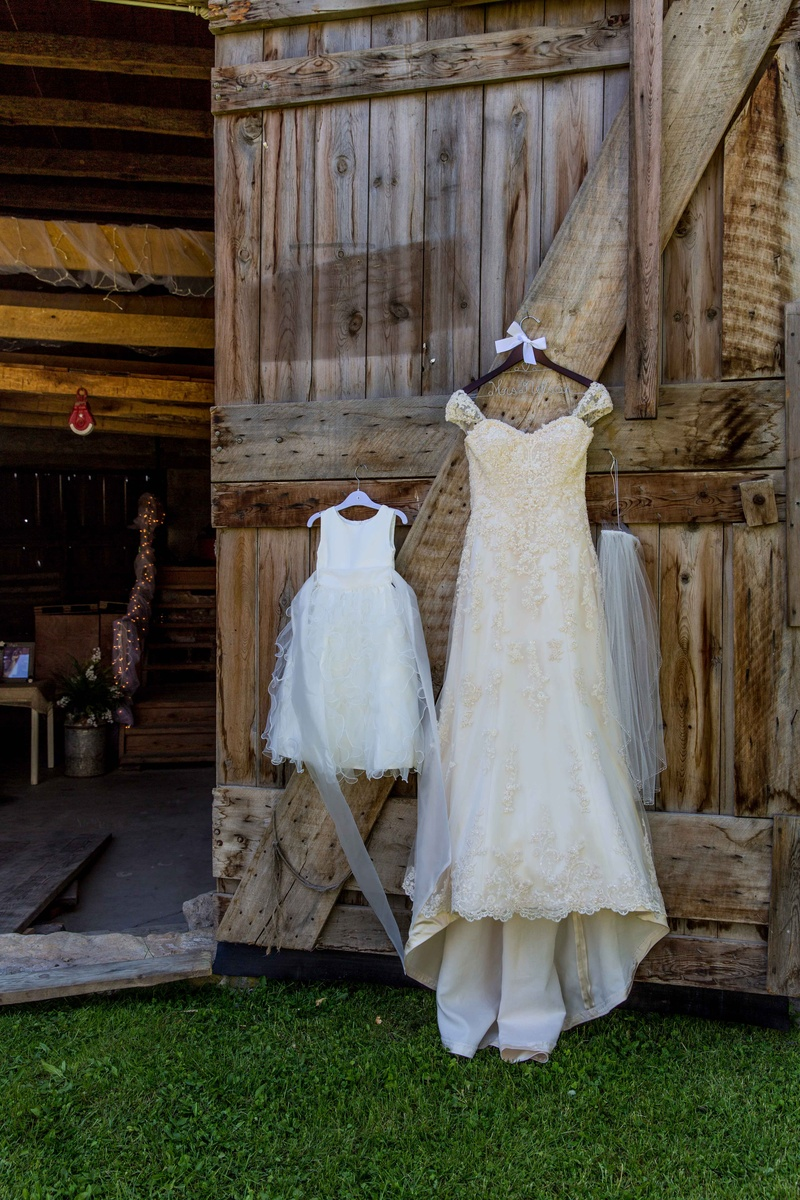 cowboy wedding dresses Ivory Maggie Sottero wedding dress hanging on barn door with flower girl dress