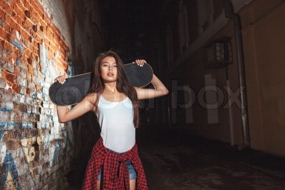 Beautiful asian teen girl with skate board on shouldres ...