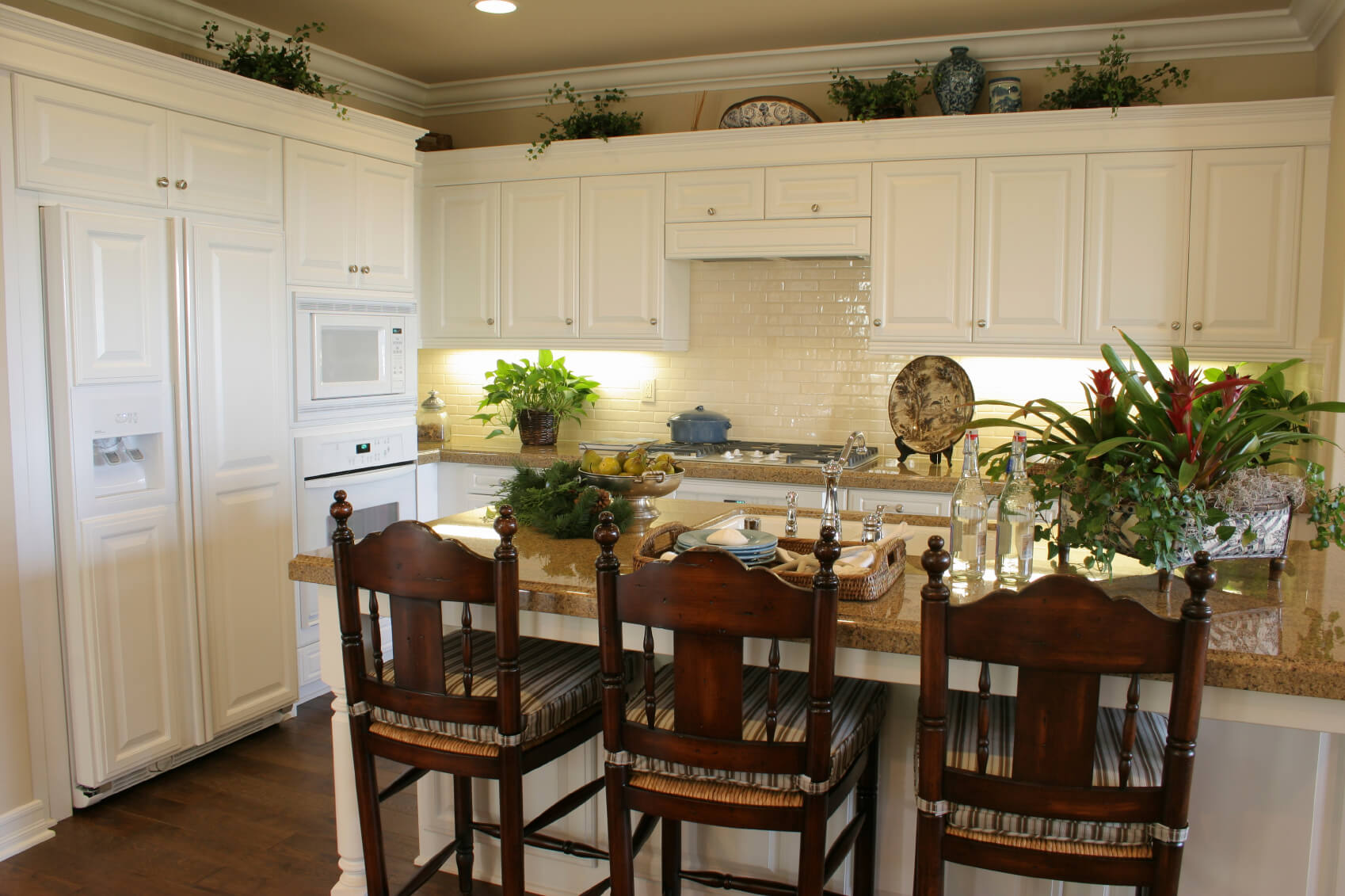 white kitchen designs pictures small kitchen white cabinets White matte cabinetry paired with glossy white brick backsplash over brown marble countertops pulls this kitchen
