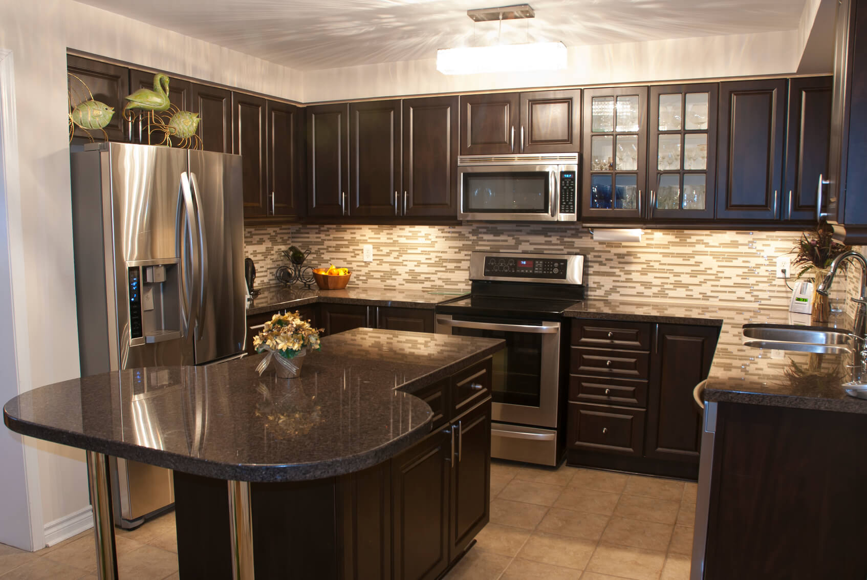 dark kitchen cabinets black kitchen countertops Cozy kitchen is stuffed with dark wood cabinetry with brushed metal hardware Black marble
