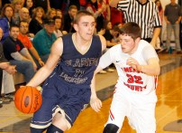 Clarion-Limestone's Noah Rankin (11) drives to the basket against Cameron County's Bryce Bauer (32) during last week's District 9 Class A Championship game. The Lions open with Cardinal Wuerl North Catholic Friday night in the state playoffs. (Photo by George Powers/www.georgepowersphotos.com)