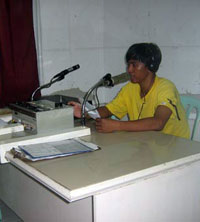 The radio booth Pace used to occupy, shown here with a colleague of the victim's. (davaotoday.com photo by Germelina Lacorte)