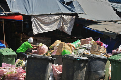 NO SEGREGATION. Davao City's implementation of the solid waste management law remains a test, as this man in Magallanes public market is seen dumping just about any kind of trash inside these bins that have been color-coded to segregate non-biodegradable and biodegradable wastes. (davaotoday.com photo by Mick M. Basa)