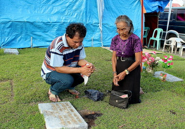 OFFERING THEIR PRAYERS.  An old woman and a man share a solemn prayer in their departed's grave in Matina village's Davao Memorial Park.  (davaotoday.com photo by Medel V. Hernani)