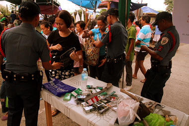 TIGHT SECURITY.  Security measures were imposed in Bankerohan village's Wireless Cemetery as cigarettes, knives , among others, were ordered to be deposited at the police table.  (davaotoday.com photo by Ace R. Morandante)