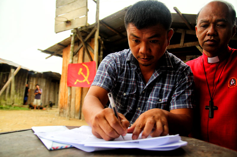 RELEASED.  SPO2 Allan Mariquit Pansoy signs his release order from the New People's Army Saturday in a village in Maco town, Compostela Valley.  He was turned over to peace advocacy group Sowing the Seeds of Peace in Mindanao and local government officials.  (davaotoday.com photo by Ace R. Morandante)