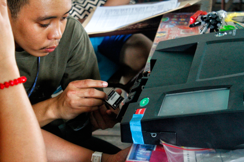 TROUBLESHOOT.  A PCOS (precinct count optical scanner) technician assists Board of Election Inspectors (BEIs) insert the CF card to the machine.  BEIs in one of the clustered precincts in Davao City's Buhangin Central Elementary School had trouble operating the machine during the final testing and sealing Monday.  (davaotoday.com photo by Marilou Aguirre-Tuburan)